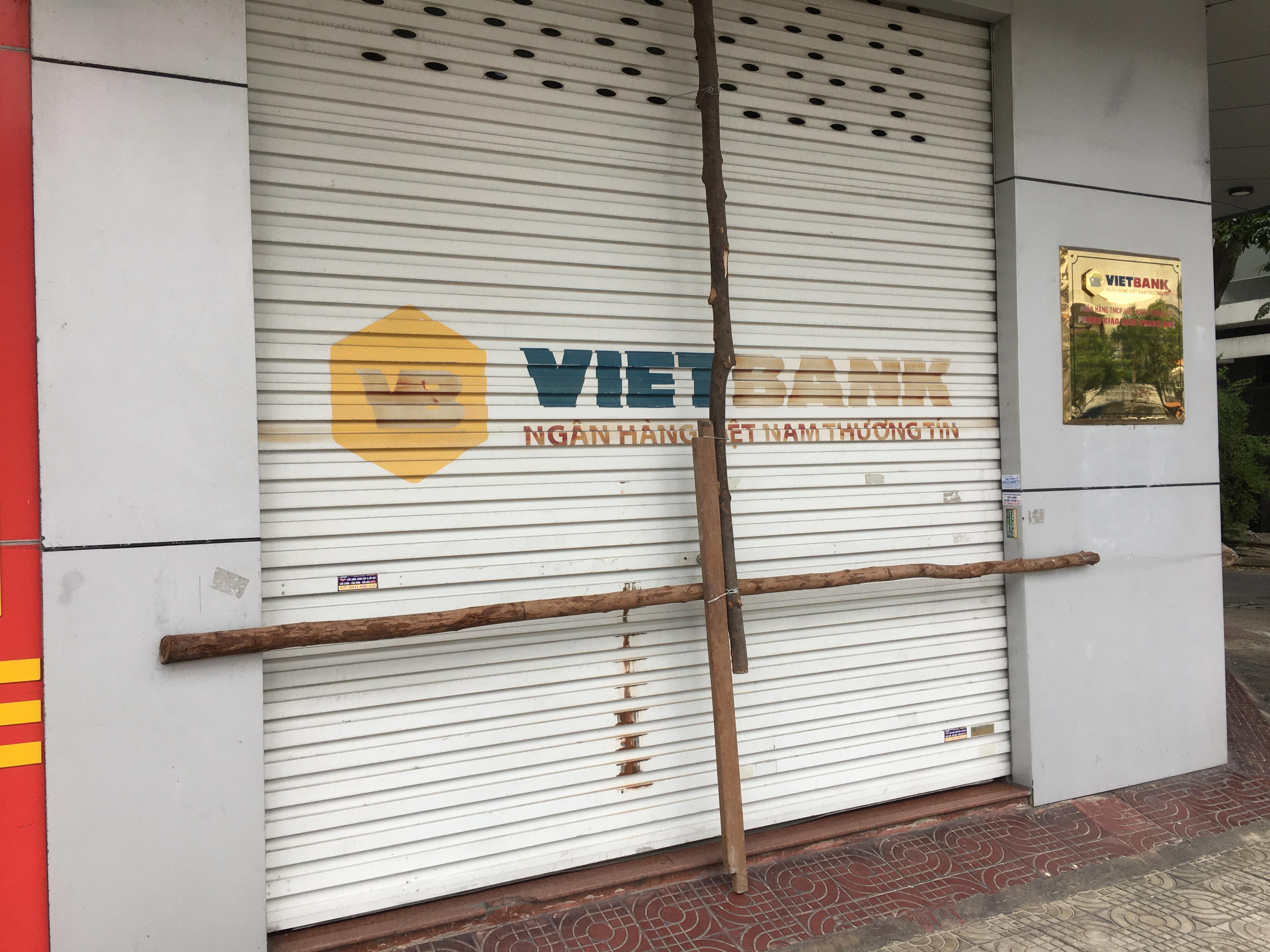 Bão số 9: Trụ ATM, ngân hàng ở Đà Nẵng tạm ngừng giao dịch, hàng loạt cửa hàng chèn chống trụ sở bằng hàng chục thanh sắt, gỗ loại lớn - Ảnh 4.