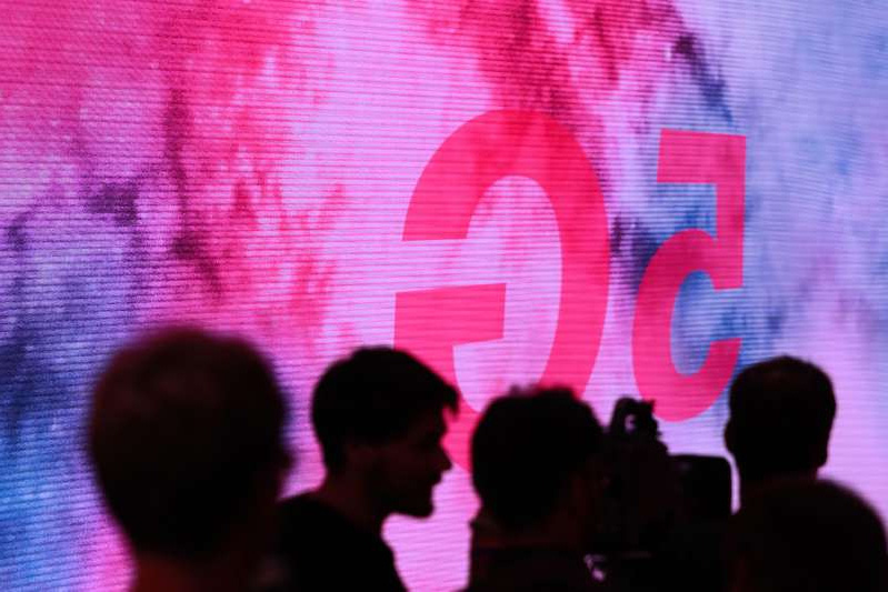 a-group-of-people-standing-in-front-of-a-crowd-attendees-are-silhouetted-beside-a-5g-display-on-the-_931616_
