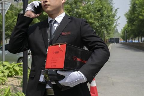 Đặt hàng xa xỉ qua mạng, shipper mặc như bán hàng đa cấp tại Trung Quốc - Ảnh 1.